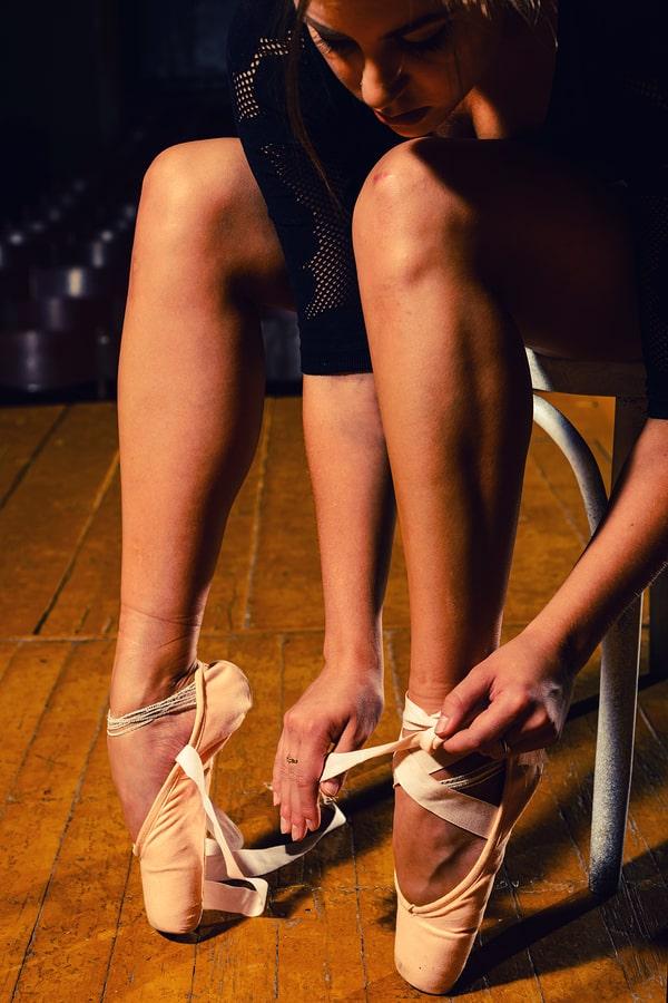 Ballerina tying up pointe shoe at ballet academy