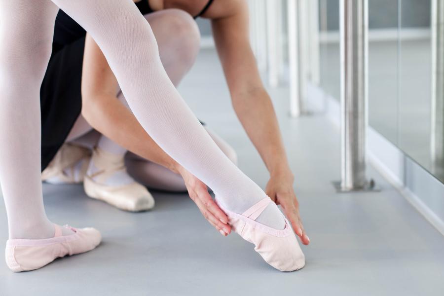 Ballet instructor teaching during ballet class for kids